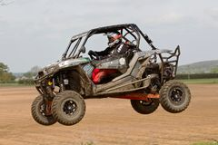 SXS racing car jump. ARNCOTT, UK - MAY 4: An unnamed driver competing in the UK SXS RZR series successfully clears the top of the table-top jump before heading Stock Photo