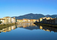 The Arno river. Along Pisa with the mountains on background and reflected in the water stock photos