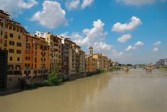 Tourism Landmark Ponte Vecchio Bridge over Arno River Florence Italy. Arno River in Florence Italy with houses and the landmark Ponte Vecchio Bridge under vivid stock photo