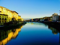 Sunset along the Arno River. The Arno River is a focal point of life in Florence, Italy. The sunset on the showcases many colors of the city royalty free stock image
