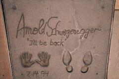 Arnold Schwarzenegger cieki i wręczają drukom Mnie ` l był z powrotem Obrazy Royalty Free