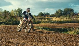Motocross MX Rider riding on dirt track Stock Photography