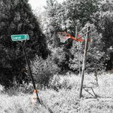 A aro e a rua quebradas de basquetebol assinam no campo coberto de vegetação imagens de stock