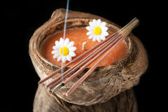 Aroma candle in coconut and incense sticks. Stock Photo