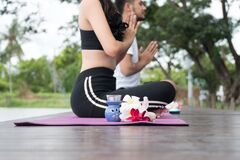 Free Aroma Candle With Plumeria Flower Beside Young Man And Woman Playing Yoga Together On Wooden Bridge . Lifestyle Exercise Couple Royalty Free Stock Images - 192635999