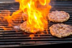 Aroma carne/del cerdo de las hamburguesas asadas a la parrilla, de la parrilla, del humo y de la luz - cocinero Fotos de archivo libres de regalías