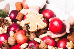 Aroma Christmas. Child's hands hold a red apple and gingerman cookie Stock Images