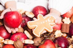 Aroma Christmas. Child's hands hold a red apple and gingerman cookie Royalty Free Stock Image