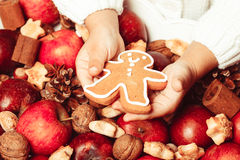 The Aroma Christmas. Child's hands hold a red apple and gingerman cookie Stock Images