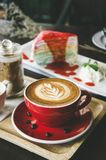 Aroma coffee red cup latte art and tasty cake on wood table in c. Offee shop with vintage dark tone and copy space stock photo