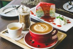 Aroma coffee red cup latte art and tasty cake on wood table in c. Offee shop with vintage dark tone and copy space stock images