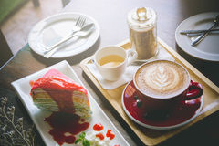 Aroma coffee red cup latte art and tasty cake on wood table in c. Offee shop with vintage dark tone and copy space royalty free stock images