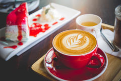 Aroma coffee red cup latte art and tasty cake on wood table in c Royalty Free Stock Photography