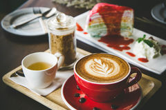 Aroma coffee red cup latte art and tasty cake on wood table in c. Offee shop with vintage dark tone and copy space royalty free stock photography