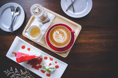 Aroma coffee red cup latte art and tasty cake on wood table in c. Offee shop with vintage dark tone and copy space stock photos