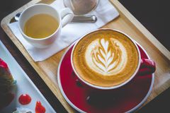 Aroma coffee red cup latte art and tasty cake on wood table in c. Offee shop with vintage dark tone and copy space royalty free stock image