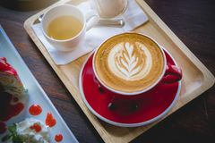 Aroma coffee red cup latte art and tasty cake on wood table in c. Offee shop with vintage dark tone and copy space stock image