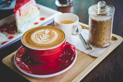 Aroma coffee red cup latte art and tasty cake on wood table in c. Offee shop with vintage dark tone and copy space royalty free stock photos