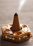 Aroma cone in a stand. With smoke close-up Stock Photos