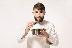 Aroma of a dish. Head chef smelling the food standing against white background. Chef smelling the aroma of a dish. stock photography