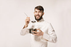 Aroma of a dish. Head chef smelling the food standing against white background. Chef smelling the aroma of a dish. royalty free stock images