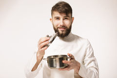 Aroma of a dish. Head chef smelling the food standing against white background. Chef smelling the aroma of a dish. stock images