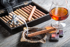 Aroma floating up from cigar and cognac in glass Royalty Free Stock Photography