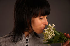 The aroma of flowers. Beautiful black brunette sniffing flowers Stock Image