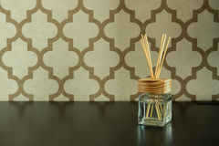 Aroma glass bottle and perfume stick on pattern wall background. Home accessories Stock Image