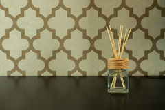 Aroma glass bottle and perfume stick on pattern wall background. Home accessories Stock Photo