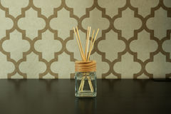 Aroma glass bottle and perfume stick on pattern wall background. Home accessories Stock Photos