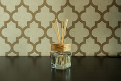 Aroma glass bottle and perfume stick on pattern wall background Stock Photo