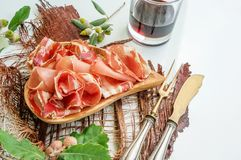 The aroma of ham and spices, thinly sliced on a white table with bread antique Cutlery and red wine.  stock images