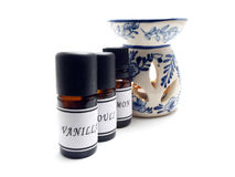 Aroma- lamp. Aroma-lamp with bottles of aromatic oils and burning candle Royalty Free Stock Images