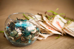 Aroma mix of dry flowers, herbs, and berries. Inside a transparent glass vase and small sachet bags Royalty Free Stock Image