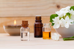 Aroma oil bottles arranged with jasmine flowers . Aroma oil bottles arranged with jasmine flowers on wooden background Royalty Free Stock Photos