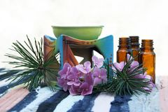 Aroma Oil in Bottles and Candle Bowl. Aromatherapy Aroma Oil in Glass Bottles and Candle Bowl Decorated Stock Photos