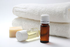 Aroma oil. Bottles of aroma oil, soap, and towels on white back ground Royalty Free Stock Photos