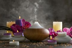 Aroma oil diffuser, candles and flowers. On table Stock Photo