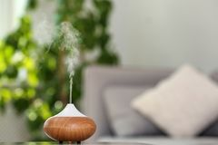 Aroma oil diffuser lamp on table blurred background. Aroma oil diffuser lamp on table against blurred background stock photos