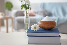 Aroma oil diffuser on stack of books. Against blurred background royalty free stock photo