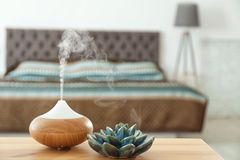 Aroma oil diffuser on table at home. Air freshener stock photo