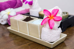 Aroma oil, facial cream, powder, towel on table Royalty Free Stock Image