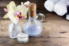 Aroma oil, orchid and candle on wooden table. Blurred massage bags and towels in background Stock Photography