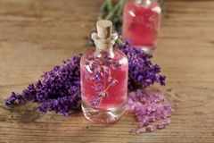 Aroma oil, sea salt and lavender flowers on wooden background royalty free stock image