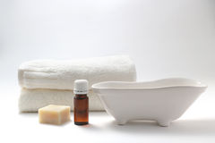 Aroma oil and spa set. Bottle of aroma oil, soap, a bathtub figurine, and towel on white back ground Stock Photo