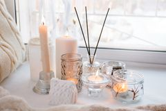Aroma stick near window with candles in the morning, winter spring cozy light monochrome background.  stock photo