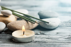 Aroma sticks, pebbles and lit candle Royalty Free Stock Photos