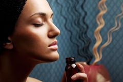Aroma therapy. Beautiful woman's face with eyes closed smelling aroma bottle royalty free stock images