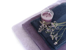 Aroma therapy and spa objects. Lilac towels arranged in a pile with purple smoking candle and aromatic plants. Isolated on white Royalty Free Stock Photography